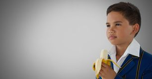 Boy against grey background with banana. Digital composite of Boy against grey background with banana Royalty Free Stock Images