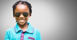Boy against grey background with sunglasses royalty free stock image