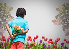 Boy against grey garden background with bunch of flowers behind back stock photo