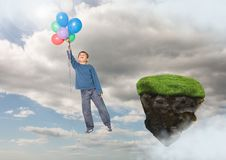 Boy floating  with balloons next to rock platform  in sky. Digital composite of Boy floating  with balloons next to rock platform  in sky Royalty Free Stock Photography