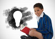 Boy reading next to charcoal light bulb. Digital composite of Boy reading next to charcoal light bulb Stock Photo