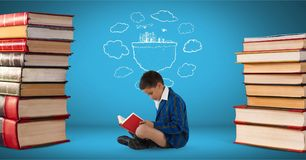 Boy reading surrounded by pile of books and a drawing with blue background. Digital composite of Boy reading surrounded by pile of books and a drawing with blue Royalty Free Stock Photos