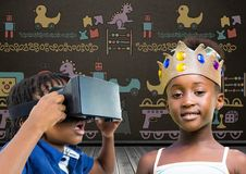 Boy with VR Headset and girl with crown in front of blackboard with toys graphics. Digital composite of Boy with VR Headset and girl with crown in front of Royalty Free Stock Photography