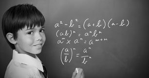 Boy writing math equations on blackboard. Digital composite of Boy writing math equations on blackboard royalty free stock photo