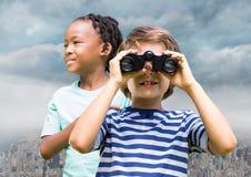Boys with binoculars over city Royalty Free Stock Photo