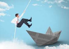 Businesman swinging on rope with paper boat in sky Royalty Free Stock Photo