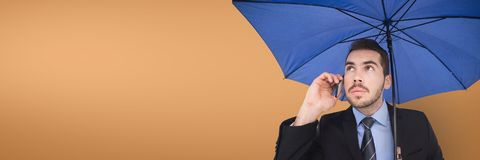 Business man with blue umbrella talking on the phone against orange background. Digital composite of Business man with blue umbrella talking on the phone against Royalty Free Stock Image