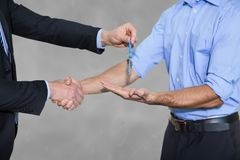 Business man giving keys and shaking hands Stock Images