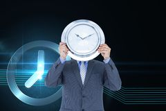 Business man holding a clock against background with clock Stock Images