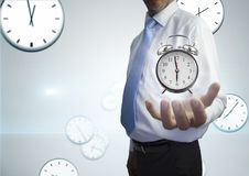 Business man holding a clock against background with clocks. Digital composite of Business man holding a clock against background with clocks Stock Photography