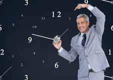 Business man holding a clock against background with clocks. Digital composite of Business man holding a clock against background with clocks Royalty Free Stock Photo