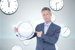 Business man holding a clock against background with clocks Royalty Free Stock Photo
