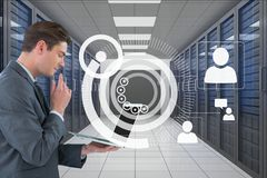 Business man holding a computer and graphics in server room. Digital composite of Business man holding a computer and graphics in server room Stock Images