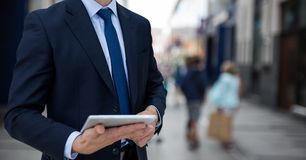 Business man holding a notebook against street background. Digital composite of Business man holding a notebook against street background Royalty Free Stock Photo