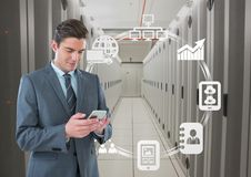 Business man holding a phone and graphics in server room. Digital composite of Business man holding a phone and graphics in server room Stock Photography