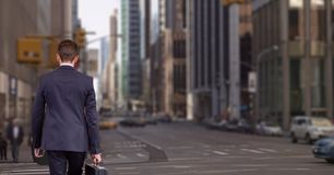 Business man holding a suitcase against city background Stock Image
