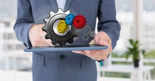 Business man holding tablet with 3 d cogs on it Royalty Free Stock Image