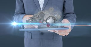 Business man holding tablet with 3 d cogs on it Stock Photo