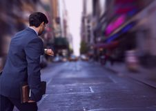 Business man looking at his clock against city background Stock Photo
