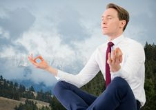 Business man meditating against mountains and trees Royalty Free Stock Image