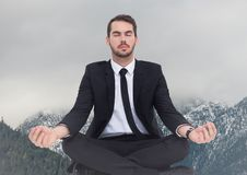 Business man meditating against snowy mountains Stock Photo