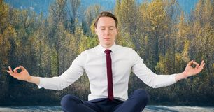 Business man meditating against trees Stock Photos