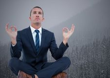 Business man meditating against trees and grey sky Stock Images