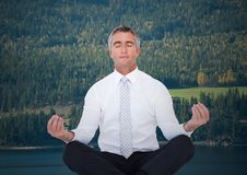 Business man meditating against trees and river Stock Photo