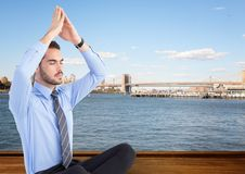 Business man meditating against water and skyline. Digital composite of Business man meditating against water and skyline Royalty Free Stock Image