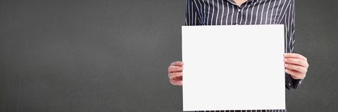 Business woman holding a blank card against grey background Royalty Free Stock Photo