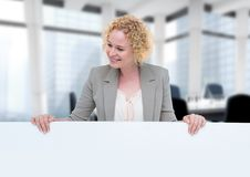 Business woman holding blank card in office. Digital composite of Business woman holding blank card in office Stock Image