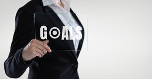 Business woman holding a glass with goals text Stock Photo