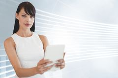Business woman holding a tablet against white and blue background Royalty Free Stock Photos