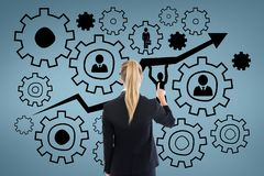 Business woman interacting with people in cogs graphics against blue background. Digital composite of Business woman interacting with people in cogs graphics Royalty Free Stock Images