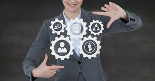 Business woman interacting with people in cogs graphics against grey background. Digital composite of Business woman interacting with people in cogs graphics Stock Photography