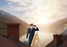 Businessman with binoculars on ladder and lake mountain landscape. Digital composite of Businessman with binoculars on ladder and lake mountain landscape Stock Photos