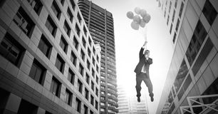 Businessman floating with balloons over surreal city buildings perspective. Digital composite of Businessman floating with balloons over surreal city buildings Stock Photos