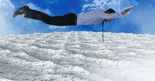 Businessman flying over sea of documents under sky clouds. Digital composite of Businessman flying over sea of documents under sky clouds Stock Images