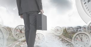 Businessman holding briefcase with surreal clocks time transition stock photos