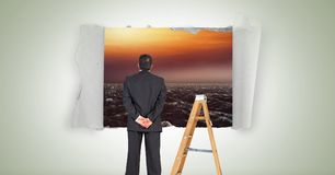 Businessman looking through paper hole with sea and ladder. Digital composite of Businessman looking through paper hole with sea and ladder Stock Photos