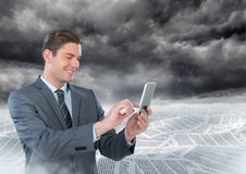 Businessman on phone in sea of documents under dark sky clouds. Digital composite of Businessman on phone in sea of documents under dark sky clouds Royalty Free Stock Images