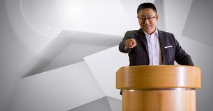 Businessman on podium speaking at conference with minimal background. Digital composite of Businessman on podium speaking at conference with minimal background Royalty Free Stock Photos