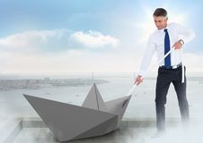 Businessman pulling paper boat with rope in city sky Stock Photos