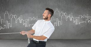 Businessman pulling rope in room with city drawings. Digital composite of Businessman pulling rope in room with city drawings Stock Photography
