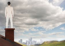 Businessman on roof chimney with city in distance Stock Images