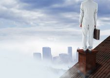 Businessman on roof chimney with city in distance Stock Photos