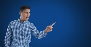 Businessman shouting and pointing angrily with blue background. Digital composite of Businessman shouting and pointing angrily with blue background Royalty Free Stock Photo