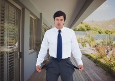 Businessman showing empty pockets outside house. Digital composite of Businessman showing empty pockets outside house Royalty Free Stock Photos