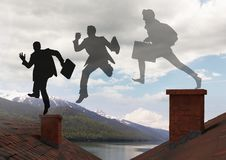 Businessman silhouettes with briefcase jumping on Roofs with chimney and mountain lake landscape. Digital composite of Businessman silhouettes with briefcase Royalty Free Stock Image
