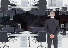 Businessman standing in inverted office with skyline. Digital composite of businessman standing in inverted office with skyline Royalty Free Stock Image
